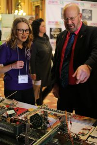 Senator Rich Taylor learning from a student during a STEM Day at the State Capitol. STEM education programs are vital in expanding the skilled workforce in Iowa.